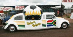 A giant football and pair of sunglasses adorn the white Beetle