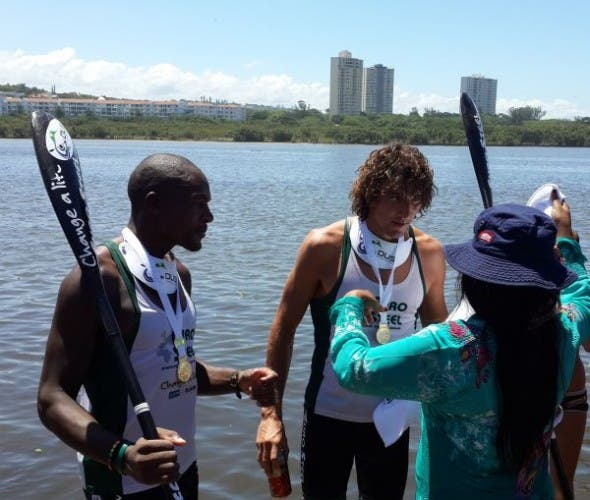 Sbonelo Zondi and Andy Birkett receive their gold medals from the MEC for art, culture, sport and recreation, Ntombikayise Sibhidla-Saphetha, at the finish of the 2014 Dusi Canoe Marathon at Blue Lagoon in Durban. (Image: Lucille Davie)