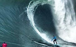 """South African big wave superstar Grant """"Twiggy"""" Baker is dwarfed by a monster wave on his way to capturing the 2014 Mavericks Invitational title (Photo: Grant Ellis, Surfer Mag)"""