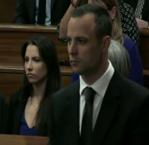 Oscar Pistorius in court today (with his sister in the background)