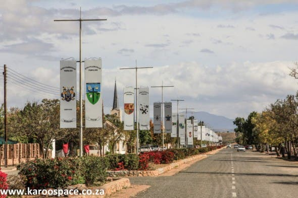 The hoisted family crests of the people of Steytlerville in the main street.