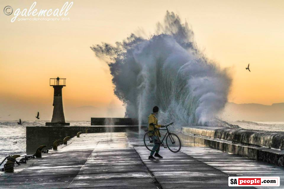 Cyclist with large wave at Kalk Bay Harbour