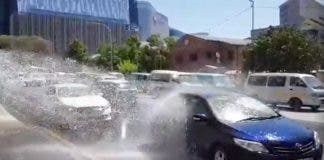 Screenshot of South African drivers turning a burst water pipe into a car wash!