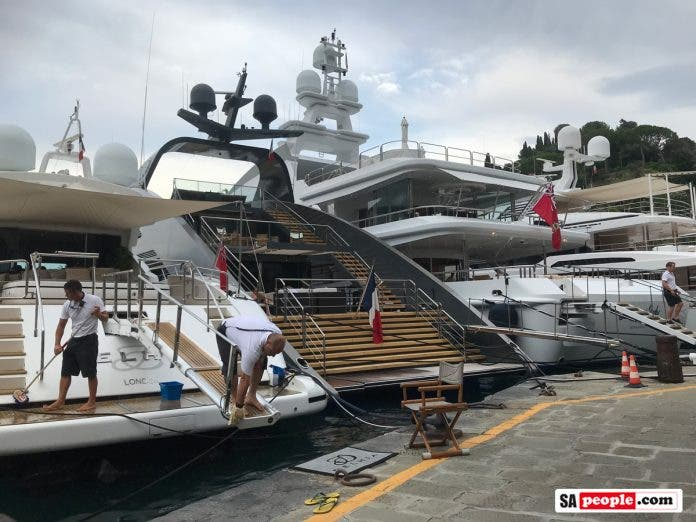 Deck hands working on yachts in Portofino, Italy