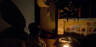 A man uses candle light during load shedding in Embo