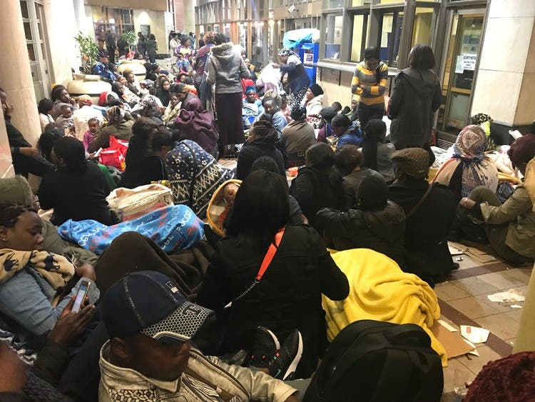 Refugees sit outside the UNHCR offices in Cape Town South Africa