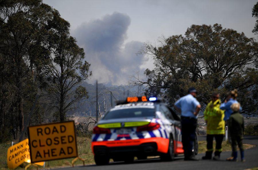 Smoke from a large bushfire is seen from a roadblock outside Wytaliba, near Glen Innes