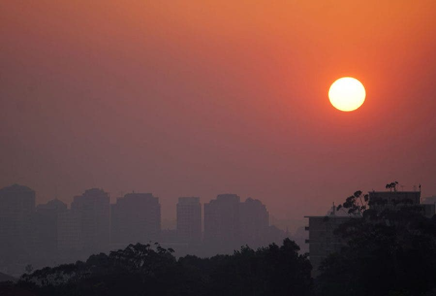 High-rise buildings are seen through smoke from bushfires during sunset in Sydney
