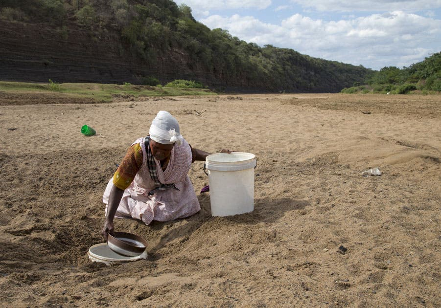 A woman gets water from a well dug in the Black Imfolozi River bed, which is dry due to drought, near Ulundi