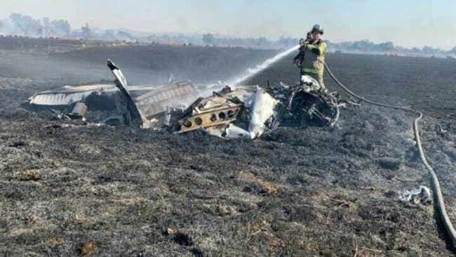 A firefighter douses down the wreckage of the plane in which rookie pilot Anika de Beer, 16, died while she was flying solo