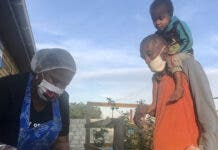 Eugene Tullex carries his son to Latifa Jacobs's soup kitchen in Kuilsriver. He used to do piecemeal jobs but he has not found work since lockdown. He is collecting for his family of six. Photo: Tariro Washinyira