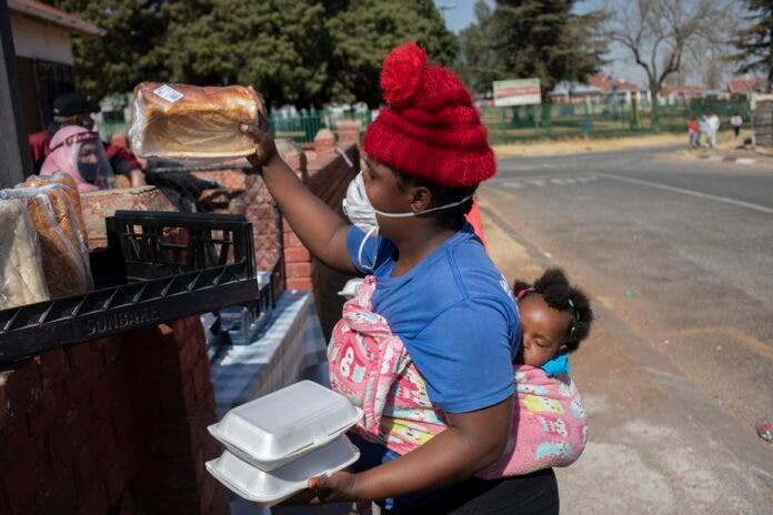 A women receives bread at the 'Hunger Has No Religion' feeding scheme run by Muslims in Johannesburg, South Africa. EFE-EPA/Kim Ludbrook