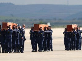 Spanish Air Force personnel carry coffins of two Spanish journalists and an Irish citizen who were killed in an armed ambush on an anti-poaching patrol in Burkina Faso, at the military airbase in Torrejon de Ardoz, Spain, April 30, 2021. REUTER/Sergio Perez