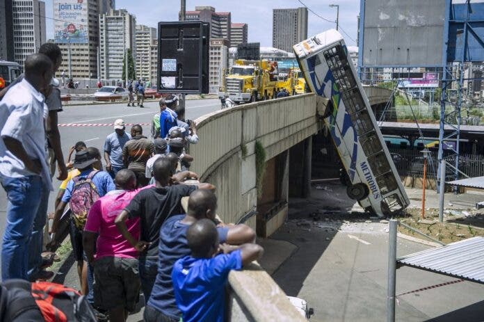 Onlookers gather on Queen Elizabeth bridge to look at a public transport bus that drove over the side of the bridge in Johannesburg, South Africa. Mujahid Safodien/AFP via Getty Images