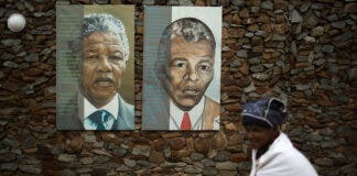 A woman walks past portraits of former South African President Nelson Mandela at the end of a memorial service in the Nelson Mandela Museum in Qunu December 10, 2013. REUTERS/Siegfried Modola/File Photo