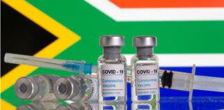 """Vials labelled """"COVID-19 Coronavirus Vaccine"""" and sryinge are seen in front of displayed South Africa flag in this illustration taken, February 9, 2021. REUTERS/Dado Ruvic/Illustration/File Photo"""