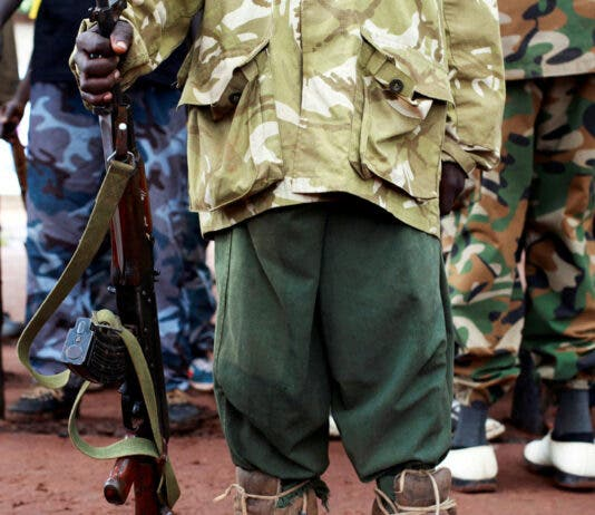 A former child soldier holds a gun as they participate in a child soldiers' release ceremony, outside Yambio, South Sudan, August 7, 2018. REUTERS/Andreea Campeanu