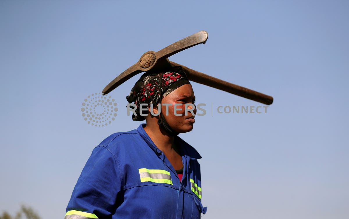 A woman arrives carrying a pickaxe on her head as fortune seekers are flocking to the village after pictures and videos were shared on social media showing people celebrating after finding what they believe to be diamonds, in the village of KwaHlathi outside Ladysmith, in KwaZulu-Natal province, South Africa, June 14, 2021. REUTERS/Siphiwe Sibeko