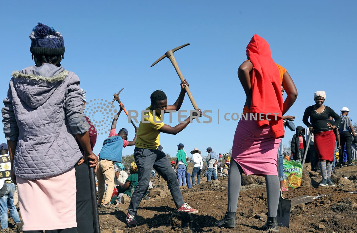 A man uses a pickaxe to dig as fortune seekers flock to the village after pictures and videos were shared on social media showing people celebrating after finding what they believe to be diamonds, in the village of KwaHlathi outside Ladysmith, in KwaZulu-Natal province, South Africa, June 14, 2021. REUTERS/Siphiwe Sibeko
