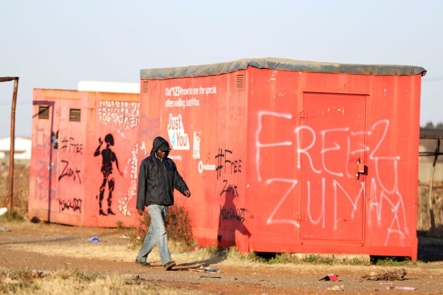 """A man walks past a graffiti with the words """"Free Zuma"""" as the country deploys army to quell unrest linked to the jailing of former South African President Jacob Zuma, in Vosloorus, South Africa, July 14, 2021. REUTERS/Siphiwe Sibeko"""