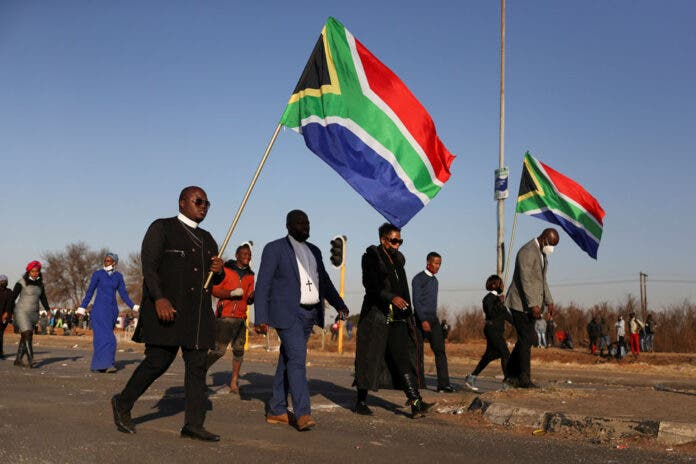 Religious leaders carrying South African flags walk near a looted shopping mall as the country deploys army to quell unrest linked to the jailing of former South African President Jacob Zuma, in Vosloorus, South Africa, July 14, 2021. REUTERS/Siphiwe Sibeko