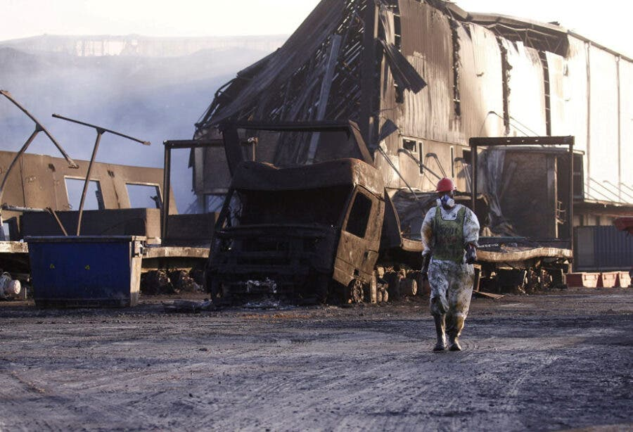 FILE PHOTO: A member of a hazardous waste cleanup crew walks to clean up a warehouse which was burned during days of looting following the imprisonment of former South African President Jacob Zuma, in Durban, South Africa, July 17, 2021. REUTERS/Rogan Ward     TPX IMAGES OF THE DAY