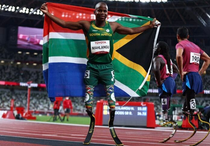 Tokyo 2020 Paralympic Games - Athletics - Men's 200m - T61 Final - Olympic Stadium, Tokyo, Japan - September 3, 2021. Ntando Mahlangu of South Africa celebrates after winning gold with the flag of South Africa whilst Regas Woods Sr of the United States and Luis Puertas of the United States look dejected REUTERS/Thomas Peter